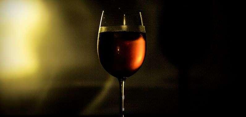 Un bicchiere di vino in penombra